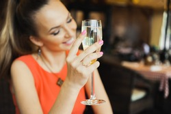 close-up portrait of a beautiful young elegant sexy blonde woman in the cafe with a glass of champagne, smiling and posing, with a ring on her finger, she is engaged