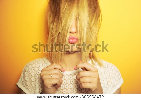 close-up portrait of a beautiful young girl sexy hipster on a yellow background is bright and smiling and posing in white blouse and hair in the tail \ with manicure and pink lips