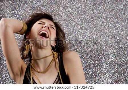 Close up portrait of a beautiful young woman dancing and singing at a party against a silver glitter background.