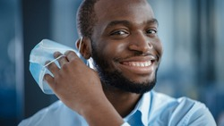 Close Up Portrait of a Black African American Handsome Male in White Shirt Taking Off a Disposable Face Mask. Successful Man Calmly Looking at Camera. Stylish Businessman or a Doctor in Hospital.