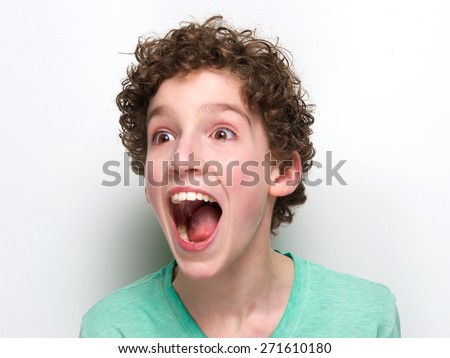 Close up portrait of a boy with mouth open having a surprised expression  #271610180