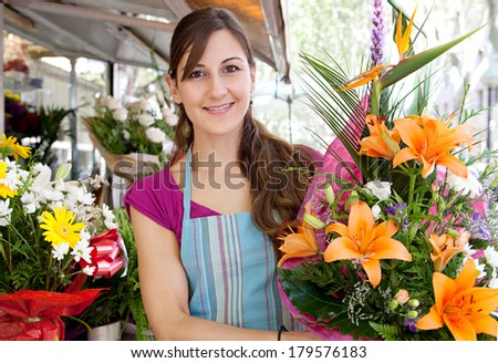 Close up portrait of a business woman florist working at her flower market shop and carrying a large bouquet of orange lilies flowers in her small business, outdoors.