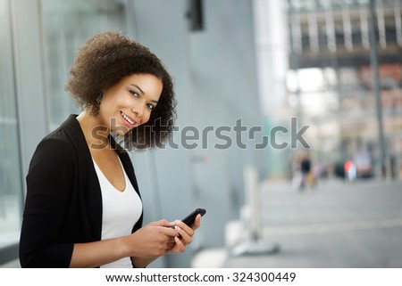 Close up portrait of a business woman smiling with cellphone #324300449