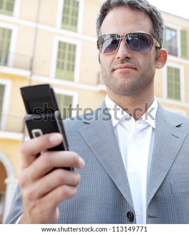 Close up portrait of a businessman using his smart phone while standing in front of a classic office building in the city.