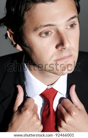 Close up portrait of a businessman with a red tie looking away, holding on to his lapels