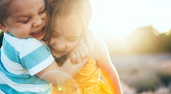 Close up portrait of a caucasian small boy embracing his sister while playing together outside