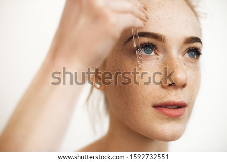 Close up portrait of a charming red haired woman with freckles applying hyaluronic serum on her face isolated on white.