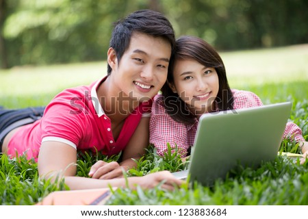Close-up portrait of a cheerful student couple lying on the lawn with laptop
