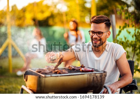 Close-up portrait of a cheerful young man grilling meat on barbecue outdoors.