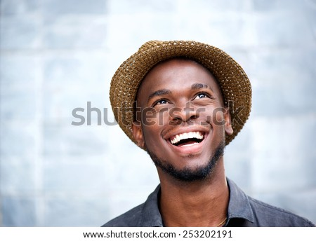 Close up portrait of a cheerful young man laughing and looking up #253202191