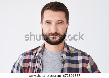 Close-up portrait of a confident young Caucasian man with beard and blue eyes looking at camera #673801537