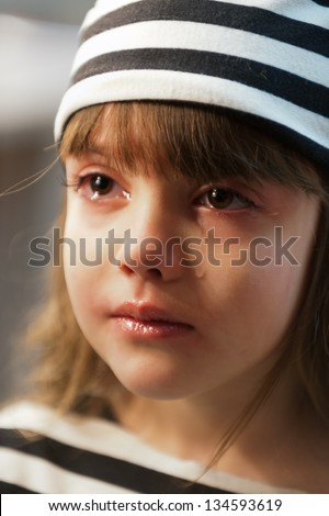 Close-up portrait of a crying little girl in a striped dress