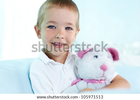 Close-up portrait of a cute boy hugging his teddy bear