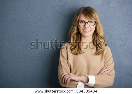 Close-up portrait of a cute cheerful middle aged woman looking at camera and smiling while standing by the wall.