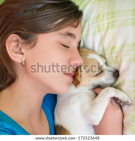 Close-up portrait of a cute girl sleeping with her little chihuahua dog