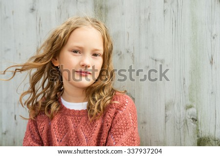Close up portrait of a cute little girl of 8 years old with curly hair, wearing  terracotta pullover, sitting against grey wooden background Stock photo ©