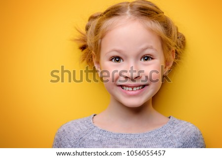 Close-up portrait of a cute little girl. Studio shot over yellow background. Childhood concept.