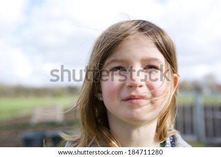 Close up portrait of a cute little girl thinking and looking up outdoors