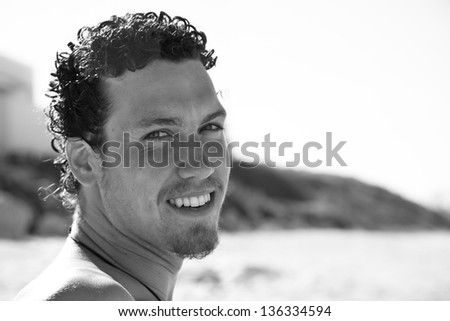 Close up portrait of a cute young man with a goatee smiling on the beach. Black and white.