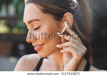 Close up portrait of a delighted young fitness girl listening to music through wireless earphones outdoors