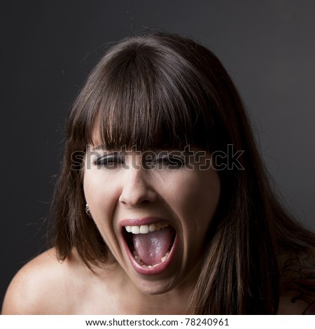 Close-up portrait of a desperate woman shouting with something, against a grey background