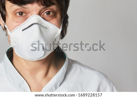 Close up portrait of a Doctor wearing a respirator N95 mask to protect from airborne respiratory diseases such as the flu, coronavirus, ebola, TB.