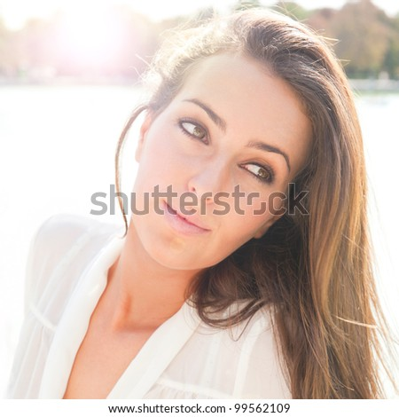 Close-up portrait of a fresh and beautiful young fashion model posing outdoor in sunny weather