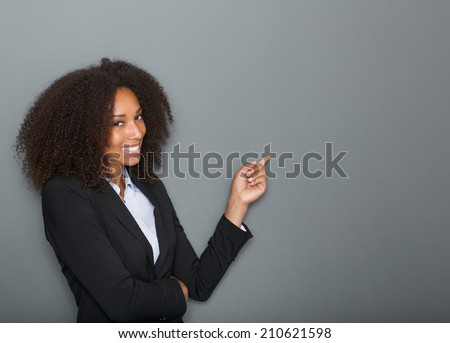 Close up portrait of a friendly business woman pointing finger on gray background #210621598