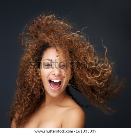 Close up portrait of a fun and happy young woman laughing with hair blowing #161033039