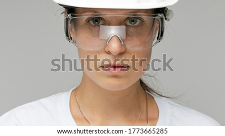 close-up portrait of a girl building in a helmet on a light background