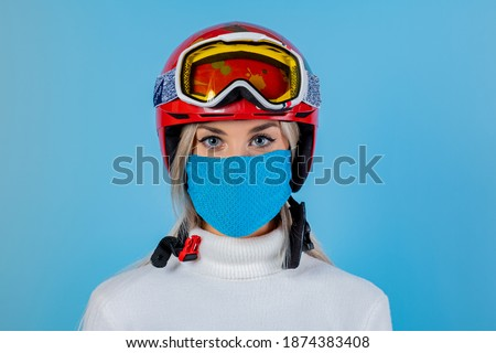 Photo of  Close-up portrait of a girl skier wearing a light blu protective mask, helmet and glasses. A snowboarder on an light blu background. Covid19 coronavirus and the ski resort pandemic