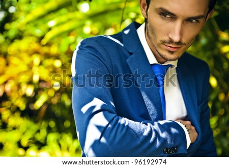Close-up portrait of a good looking beautiful young man in costume outdoors.