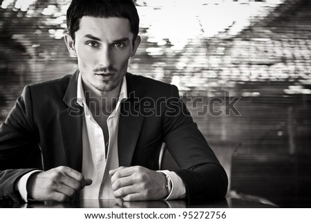 Close-up portrait of a good looking beautiful young man in costume outdoors. Black-white photo. - stock photo