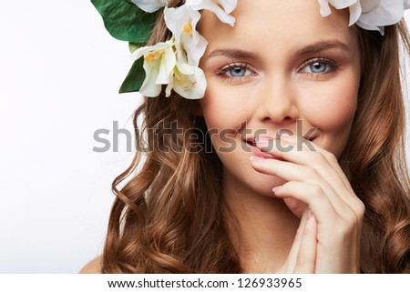 Close-up portrait of a gorgeous girl with flower hairstyle covering her smile with her hand