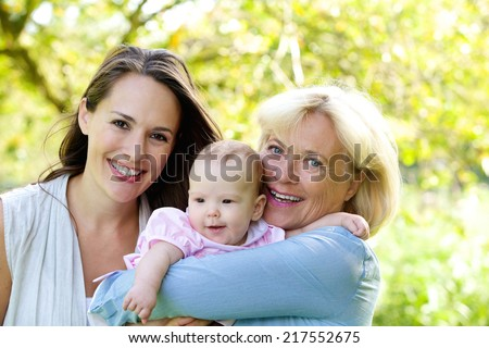 Close up portrait of a grandmother and mother smiling with baby