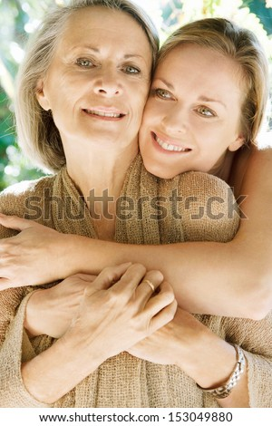 Close up portrait of a grown daughter and her mature mother hugging and loving each other during a sunny day in a home garden, being together and smiling outdoors.