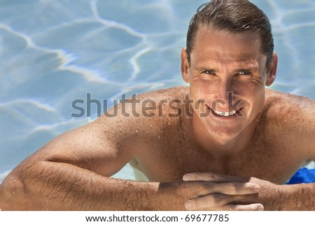 Close up portrait of a handsome and happy mid aged man relaxing resting on his hands at the side of a sun bathed swimming pool smiling with perfect teeth.