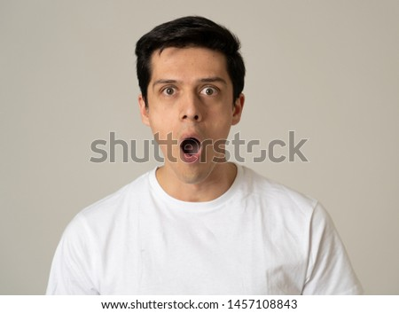Close up portrait of a handsome caucasian young man with a surprised and shocked face. Attractive male looking amazed with wide eyes and mouth open in surprise. Human facial expressions and emotions. #1457108843