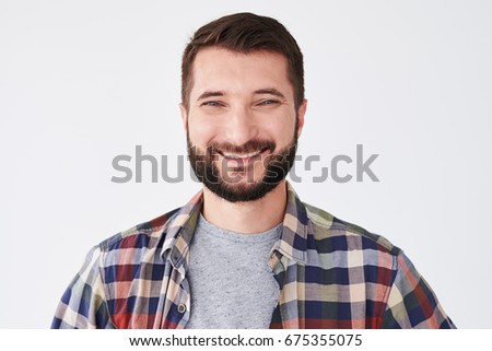 Close-up portrait of a handsome man with a smile on his face. Fashion portrait of an attractive young bearded man in the studio - Shutterstock ID 675355075