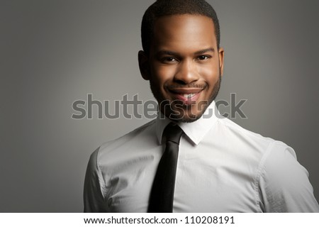 Close up portrait of a handsome young African American businessman smiling in studio with gray background