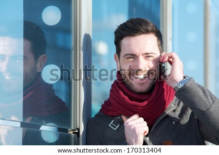 Close up portrait of a handsome young man smiling and calling by mobile phone outdoors - Shutterstock ID 170313404