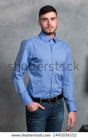 Close-up Portrait of a handsome young man standing in interior on gray background #1445036552
