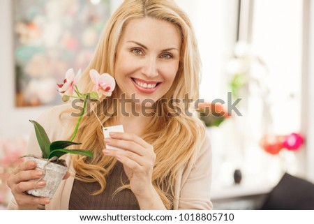 Close up portrait of a happy beautiful mature woman smiling to the camera joyfully holding an orchid in a pot shopping at the home decor store copyspace beauty femininity apartment retail sales.