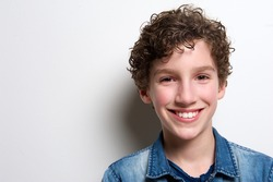 Close up portrait of a happy boy smiling on white background