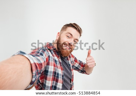 Shutterstock Close up portrait of a happy casual man taking selfie and showing thumbs up gesture over white background