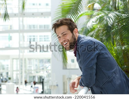 Close up portrait of a happy man leaning inside bright building