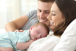 Close up portrait of a happy parents watching their baby sleeping on a bed at home