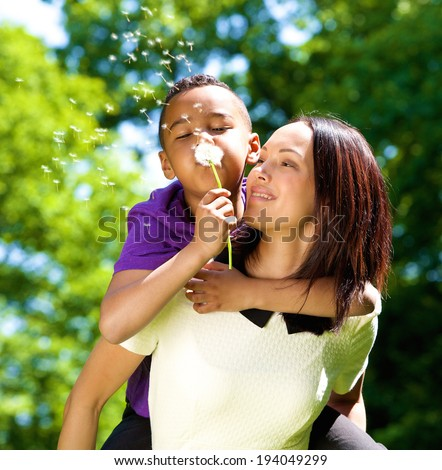 Close up portrait of a happy single mother with son blowing dandelion