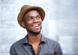 Close up portrait of a happy young african american man laughing against gray background