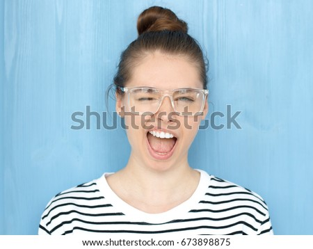Close up portrait of a happy young hipster european teen girl in nerdy square glasses blinking at camera in a playful manner, smiling and winking, shouting loudly, standing against blue background #673898875